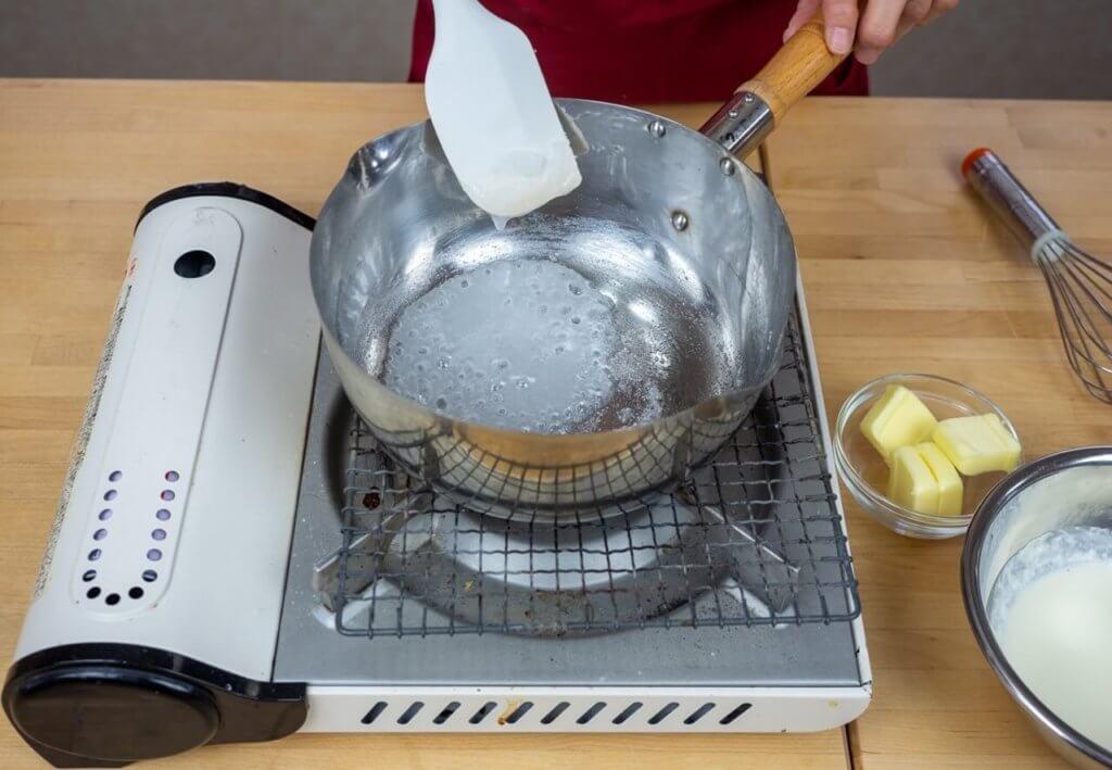 熱している鍋に砂糖、水あめ、水が煮立っている様子