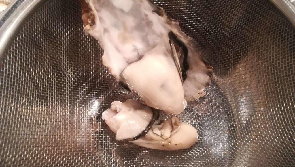 牡蠣の中身をざる移す様子