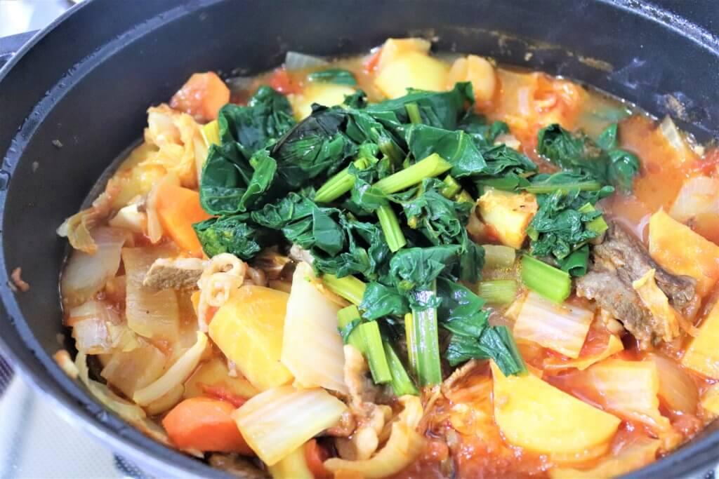 野菜や肉を煮込んだ鍋に、ビーツの葉を加える様子