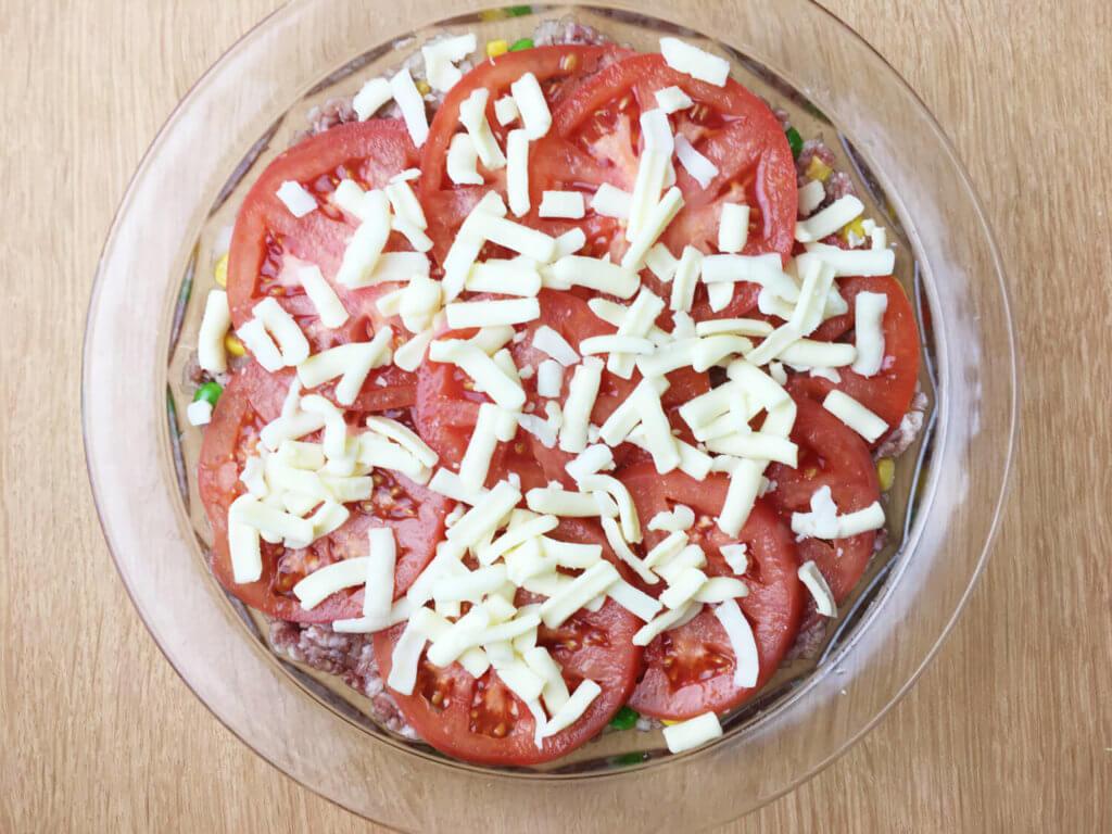 平らに伸ばした材料の上に、トマトやチーズを乗せた様子