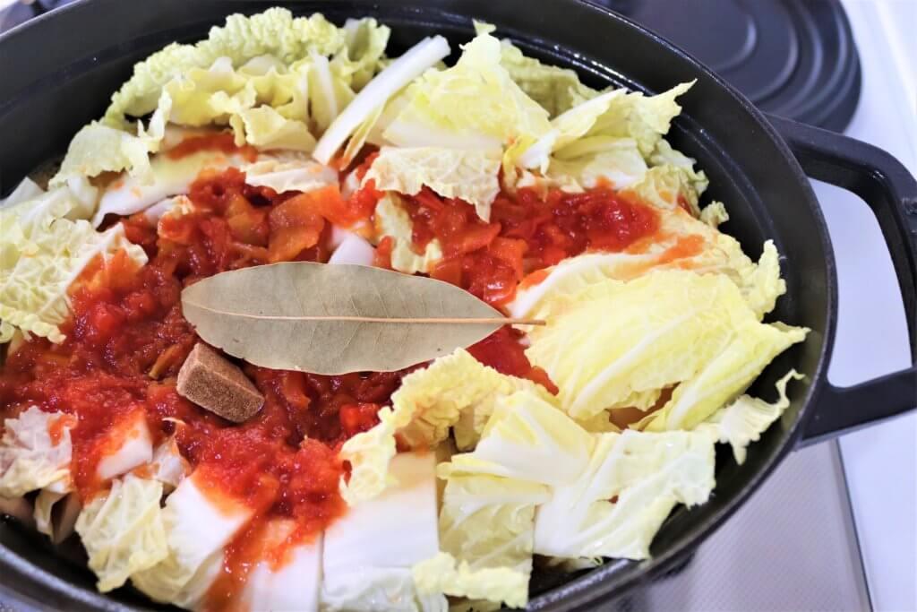 白菜の次に、ローリエ、トマト、ブイヨンを鍋に入れる様子