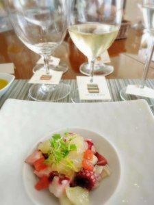 お皿に魚のマリネ、隣に白ワインが並んでいる様子