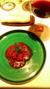 お皿にエビチリ、隣に赤ワインが並べられている様子